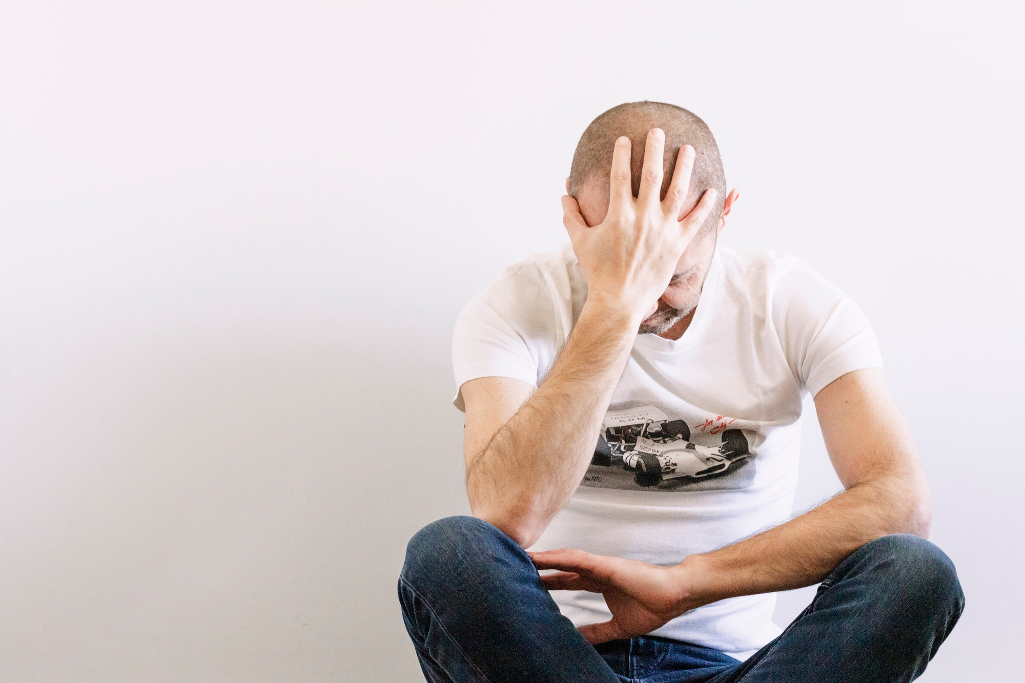 Man looking depressed with a hand in the head