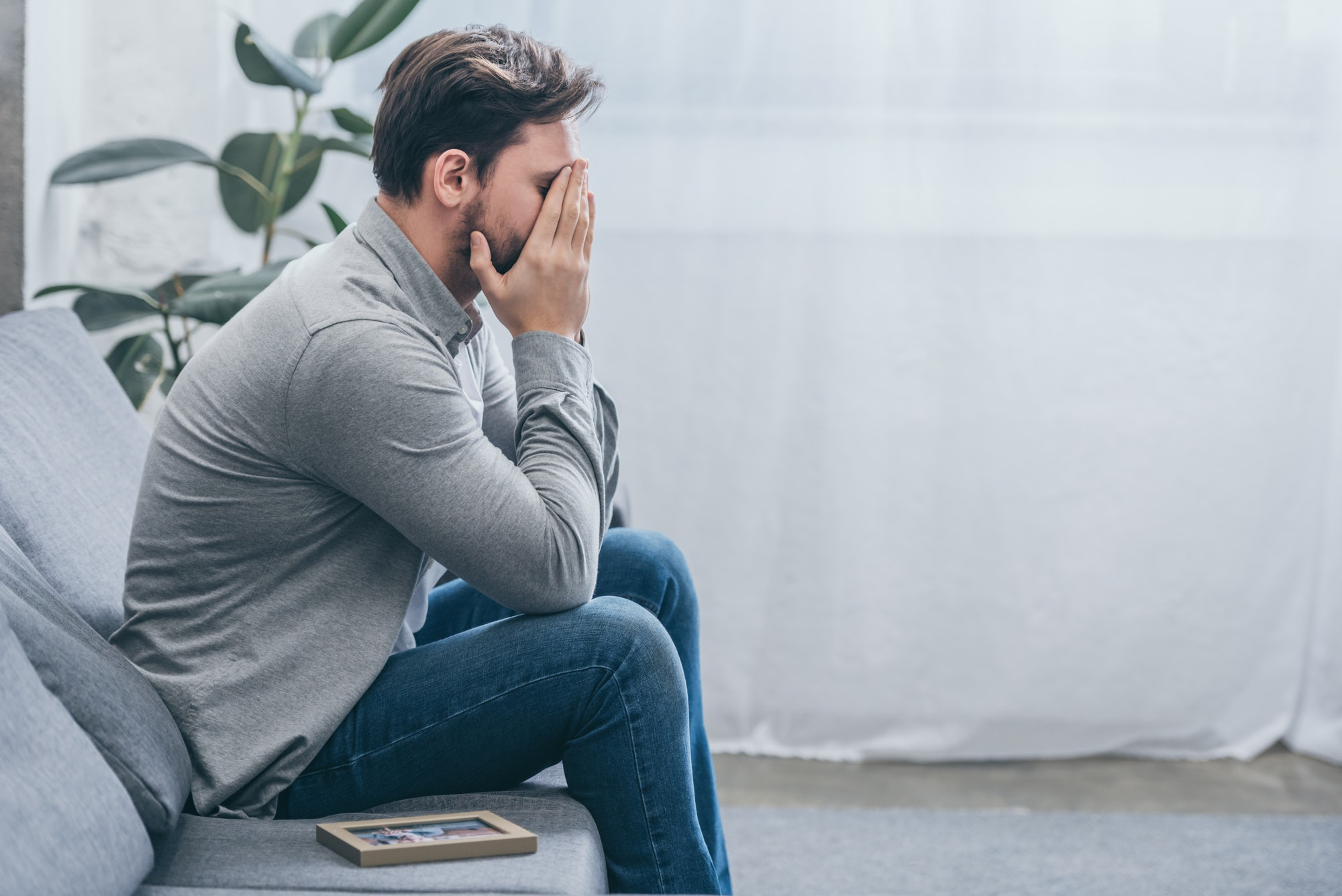 man sitting on grey couch with photo in frame and crying at home, grieving disorder concept