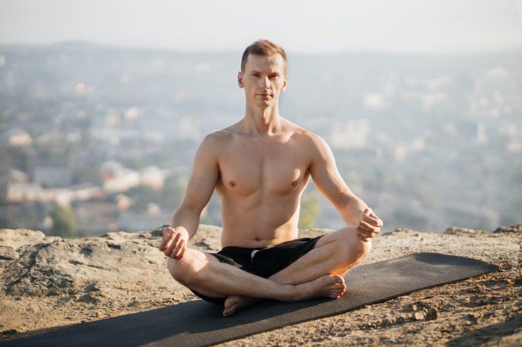 Relaxed shirtless man practising yoga on fresh air, meditating
